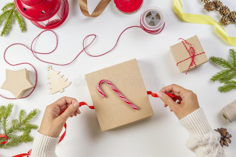 Christmas gift wrapping. Woman`s hands packing Christmas present box on white table background stock photos