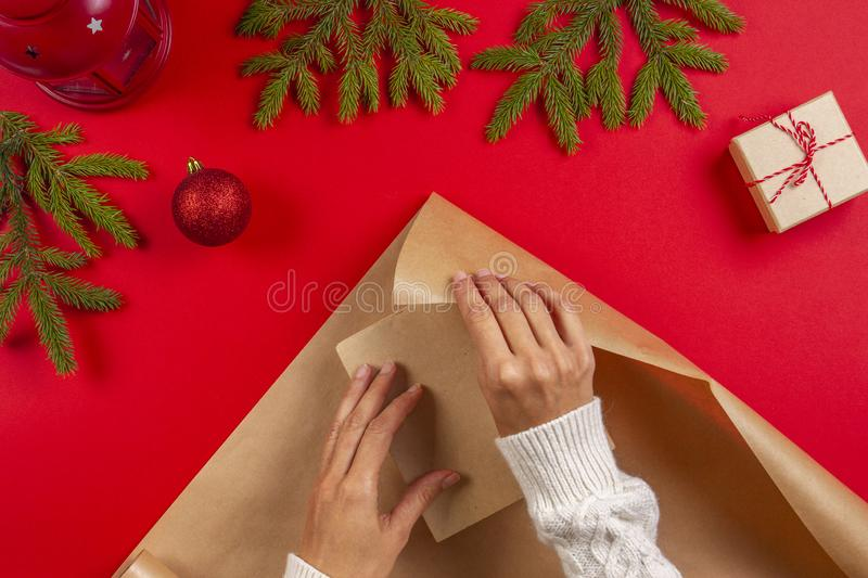Christmas gift wrapping. Woman`s hands packing Christmas present box in craft paper stock photo