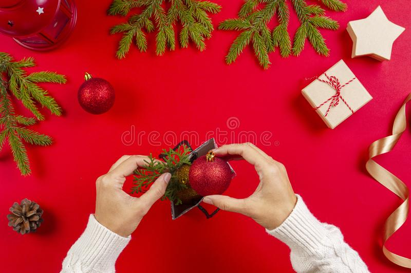 Christmas gift wrapping. Woman`s hands packing Christmas presents on red background stock photos
