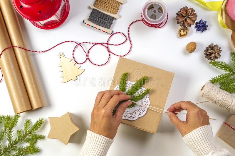 Christmas gift wrapping. Woman`s hands packing Christmas presents on white table stock photography