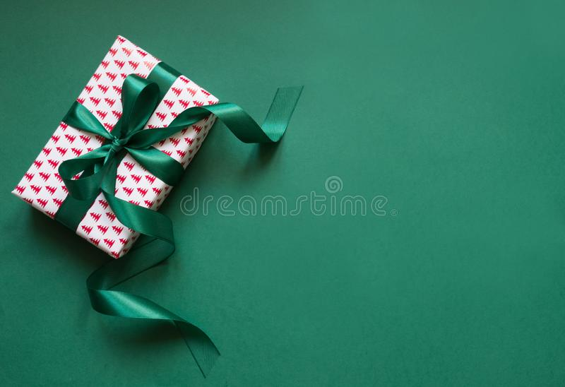 Christmas giftbox with green ribbon on green surface. Space for wishes. Holiday card. Top view royalty free stock images