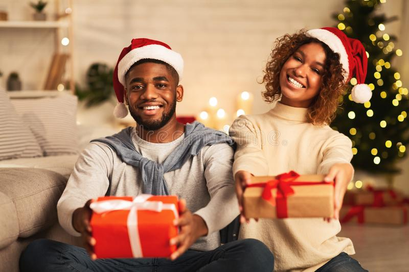 Christmas gifts. Black couple holding presents and smiling royalty free stock photography