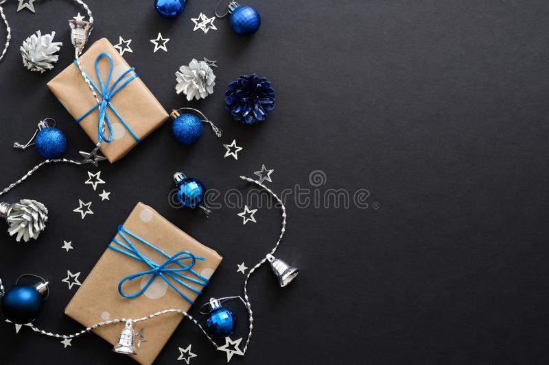 Christmas gifts with blue ribbon, blue balls, fir tree branches, cones, confetti on dark black background with copy space. Flat. Lay, top view, overhead royalty free stock images