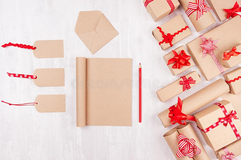 Christmas gifts boxes, blank labels and notepad for your text of kraft paper with red bows and ribbon on soft white wood board. Christmas gifts boxes, blank royalty free stock photo