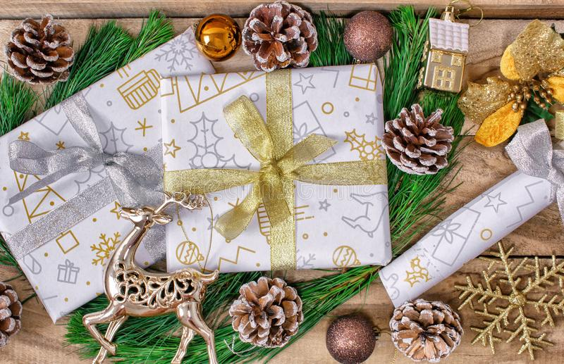 Christmas gifts, boxes of gifts, fir, with cones and deer on a wooden background. stock images