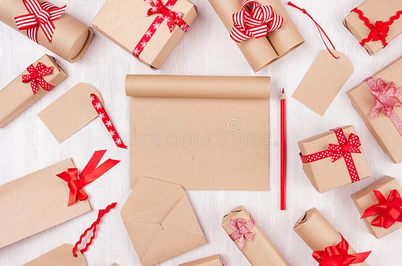 Christmas gifts boxes with red ribbons, blank notepad and red pencil on white wood board as celebration background for your design royalty free stock photography