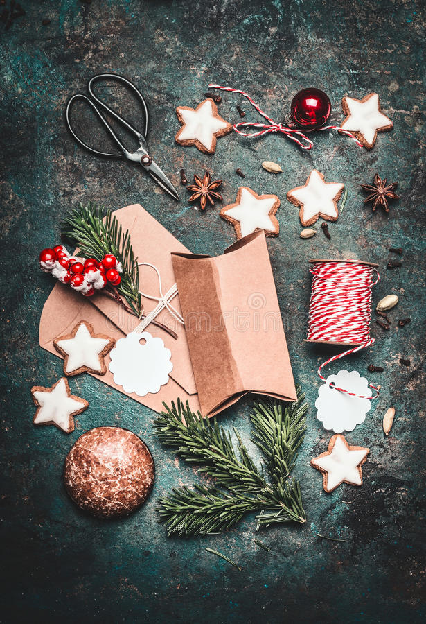 Christmas gifts decoration and making. Festive gift Cardboard boxes, ribbon, fir brunches, cookies and Gingerbread, scissors and C royalty free stock image