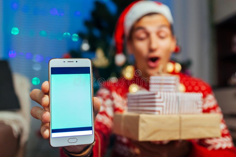 Christmas gifts delivery. Man ordered New year presents using smartphone. Happy guy holding gift boxes and phone royalty free stock images