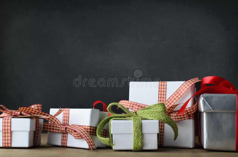Christmas Gifts on Desk with Blackboard Background stock images