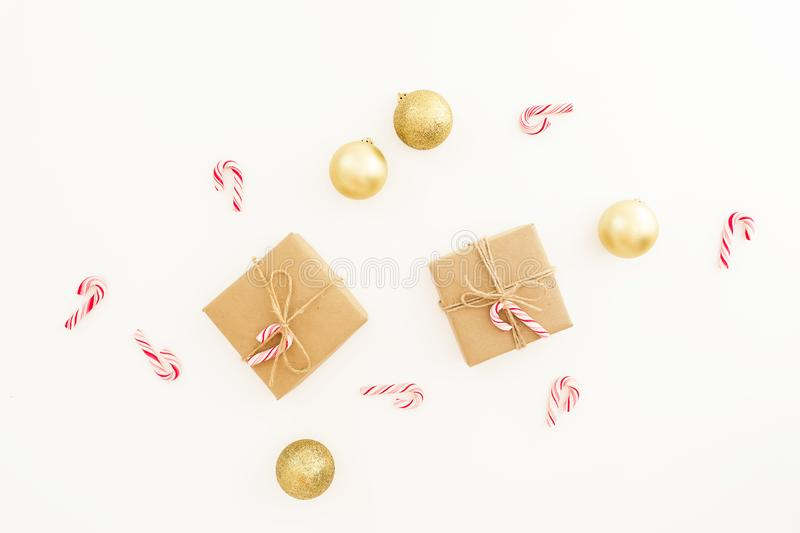 Christmas gifts, golden decorations and candy canes on white background. Flat lay, top view. New Year composition royalty free stock photo