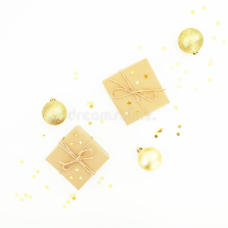 Christmas gifts, golden decorations and confetti on white background. Flat lay, top view. Christmas composition royalty free stock photo