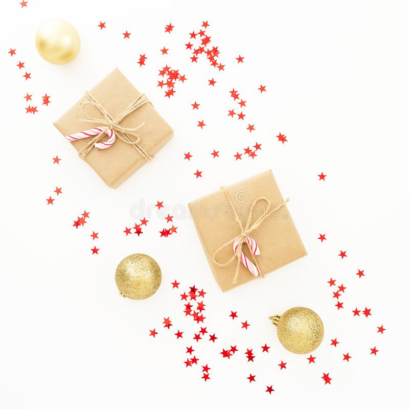 Christmas gifts, golden decorations and red confetti on white background. Flat lay, top view. Christmas composition royalty free stock image