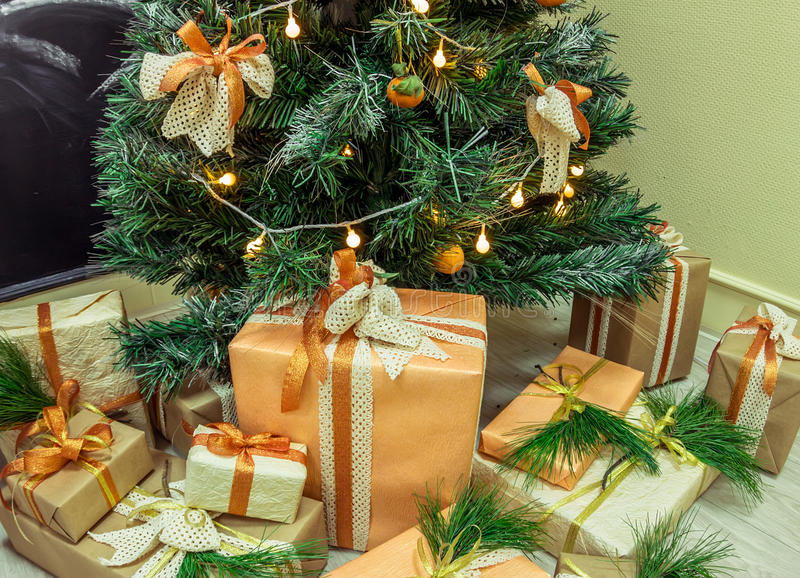 Christmas gifts in kraft bumane under the Christmas tree.  royalty free stock photography