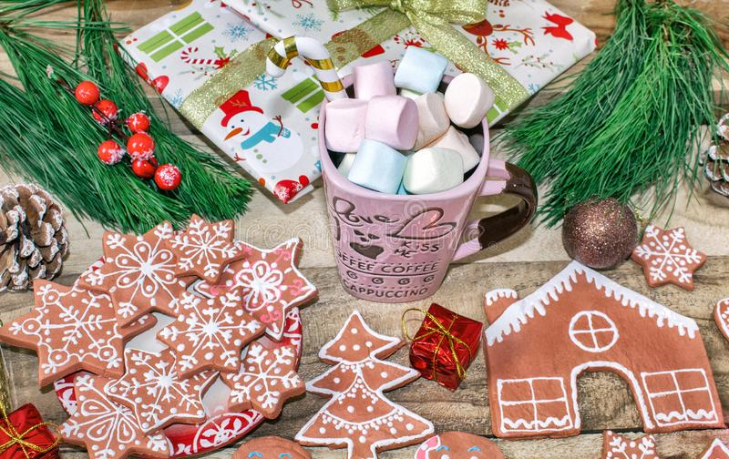 Christmas gifts, a mug of marshmallows. Ginger cookie. Gingerbread house, gingerbread man, stars and spruce on wooden background. stock image