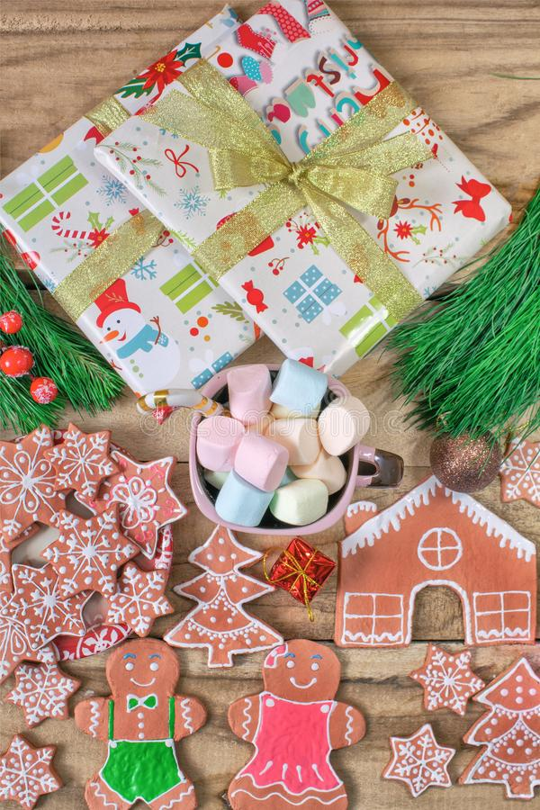 Christmas gifts, a mug of marshmallows. Ginger cookie. Gingerbread house, gingerbread man, stars and spruce on wooden background. Festive background royalty free stock photos