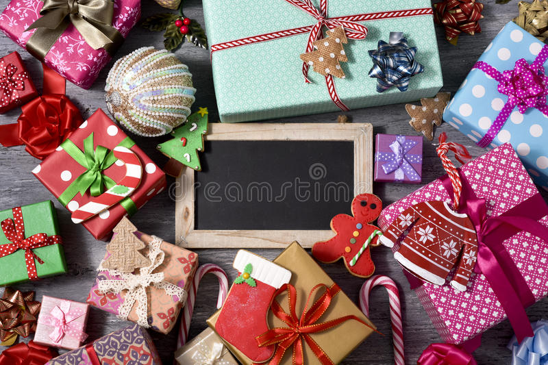 Christmas gifts and ornaments, and blank chalkboard royalty free stock images