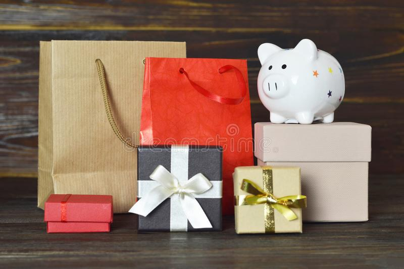 Christmas gifts and piggy bank on wooden background. Christmas gifts and ceramic piggy bank on wooden background royalty free stock image
