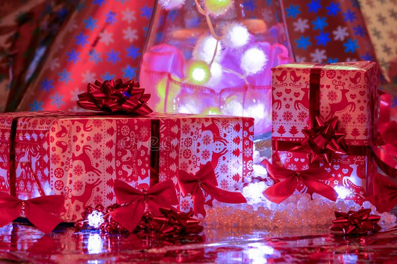 Christmas gifts posed in front of colorful illuminations. Xmas packing Red and white with decorations multicoloured royalty free stock image