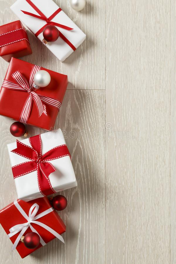Christmas gifts presents on rustic wood background. Simple, red and white gift boxes festive holiday border. stock image
