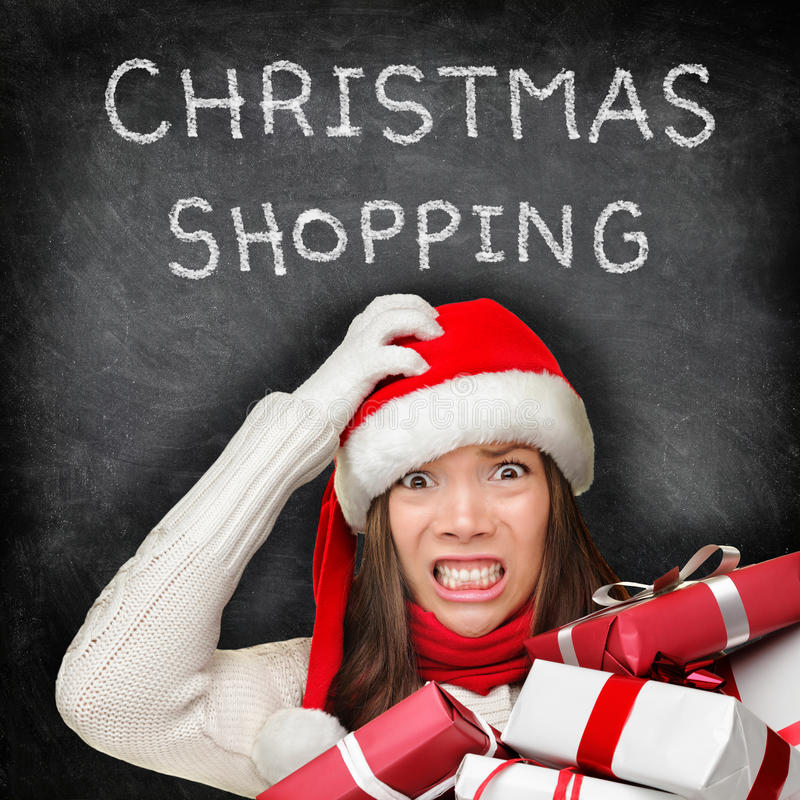 Christmas gifts shopping woman - holiday stress. Christmas gifts shopping woman holiday stress. Stressed girl buying presents wearing red santa hat looking royalty free stock photography