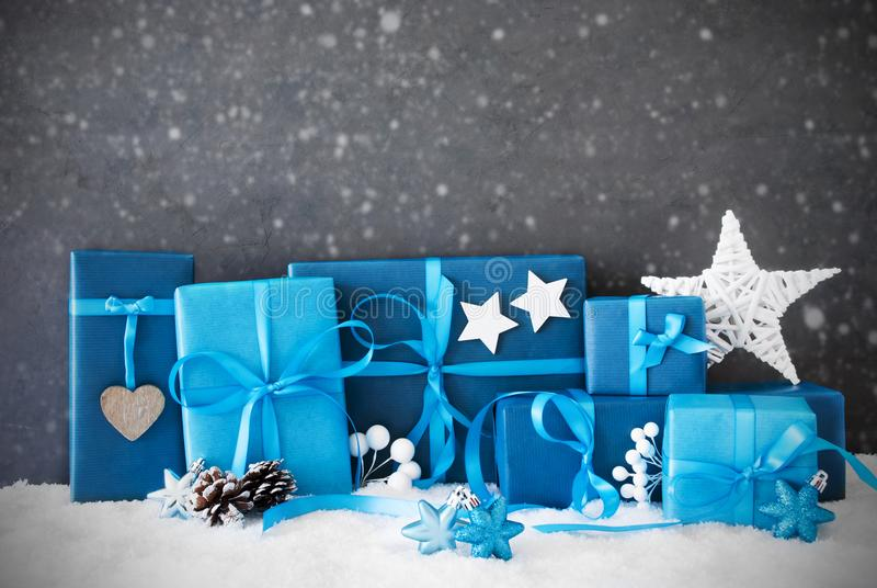 Christmas Gifts, Snow, Copy Space,Snowflakes. Concrete Wall With Copy Space For Advertisement. Blue Christmas Gifts With Decoration Like Stars And Fir Cone On stock photo