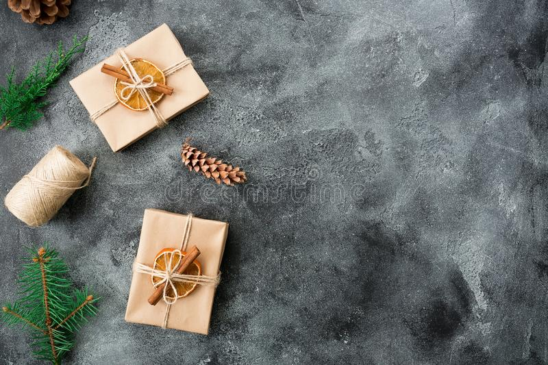 Christmas gifts, winter plants and cones on dark background. Winter composition. Flat lay. Top view stock photo