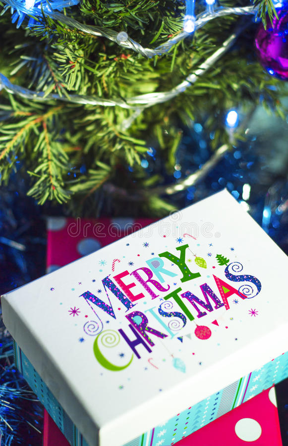 Christmas gifts and the words Merry Christmas. On the background of the Christmas tree and lights stock photos
