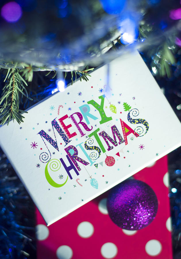 Christmas gifts and the words Merry Christmas. On the background of the Christmas tree and lights stock image