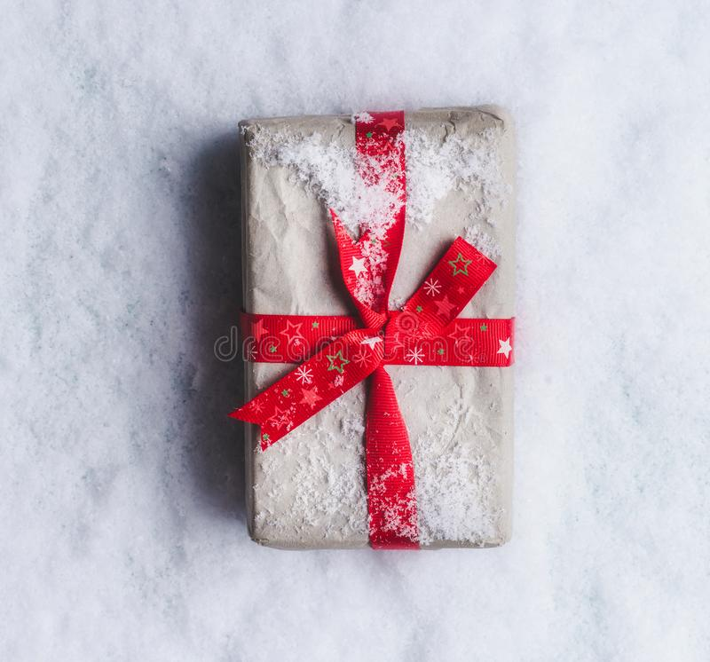 Christmas gifts wrapped in craft paper with red ribbon on snow background, top view with copy space for your greeting design. stock photography