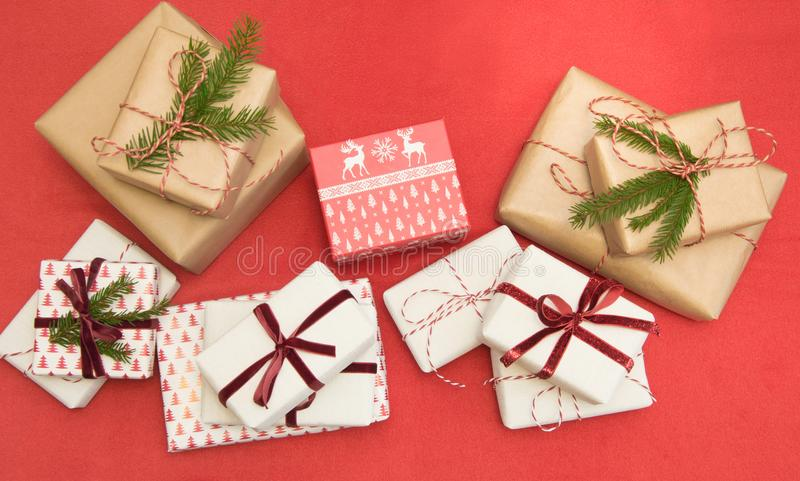 Christmas gifts wrapped in ornament paper and decorative red rope ribbon on red surface. Creative hobby, top view. Prepare to Xmas royalty free stock photo