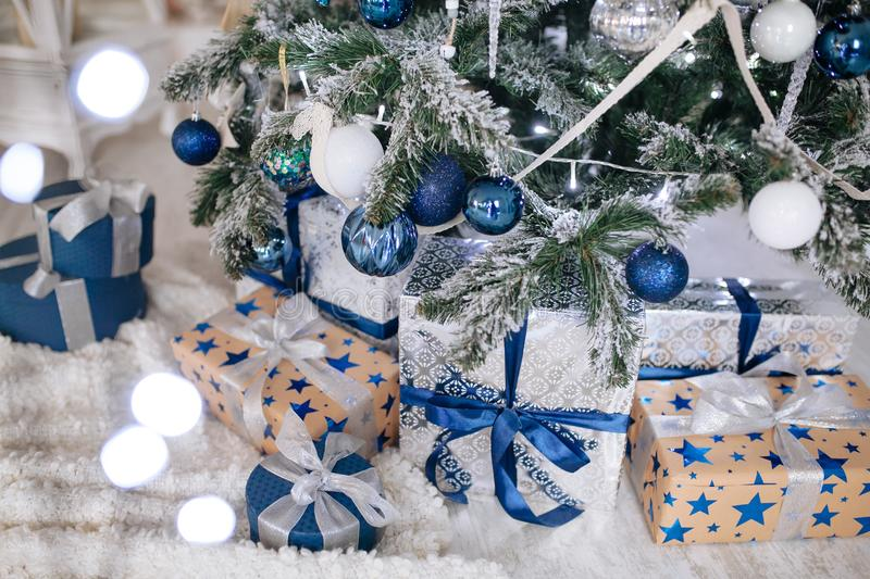 Christmas Gifts wrapped in silver and blue paper, background with xmas lights bokeh of blurred under Christmas tree. royalty free stock photo