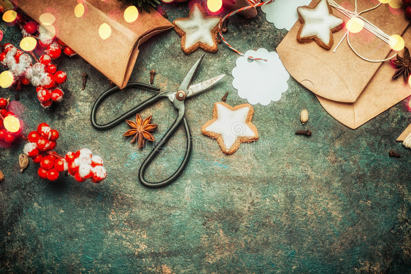 Christmas gifts wrapping with brown cardboard boxes , shears, holiday star cookies and festive decorations, top view stock photos