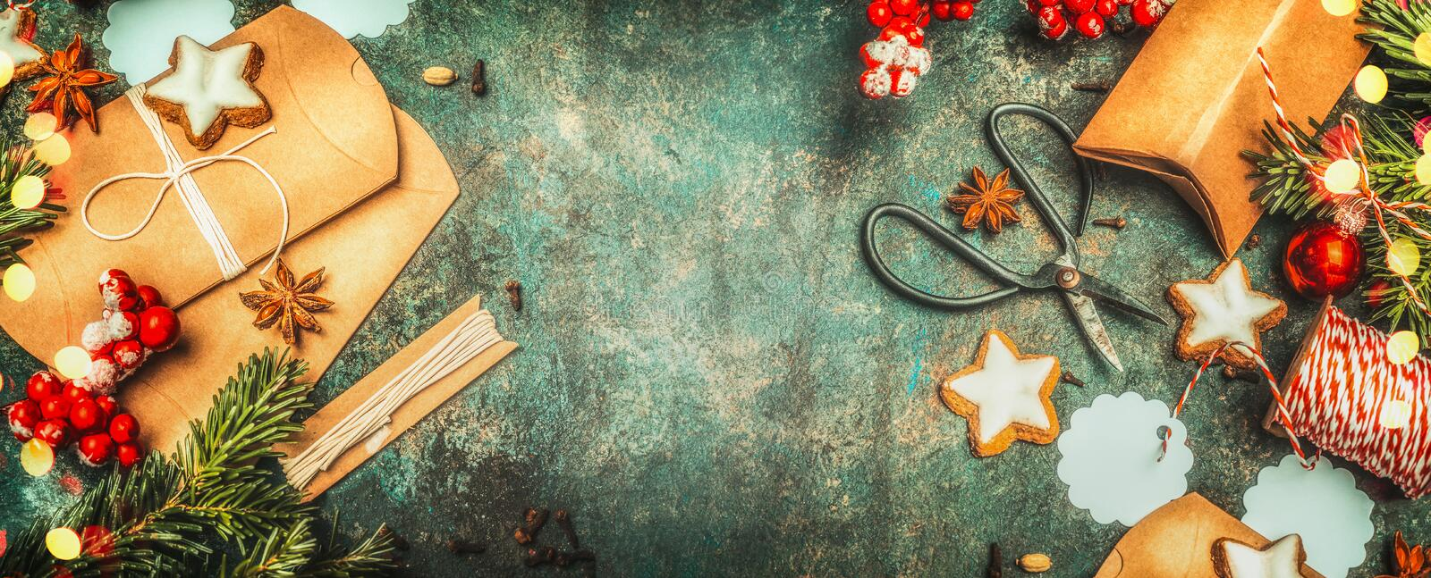Christmas gifts wrapping with little cardboard boxes , shears, holiday cookies and festive decorations on vintage background, top stock photos