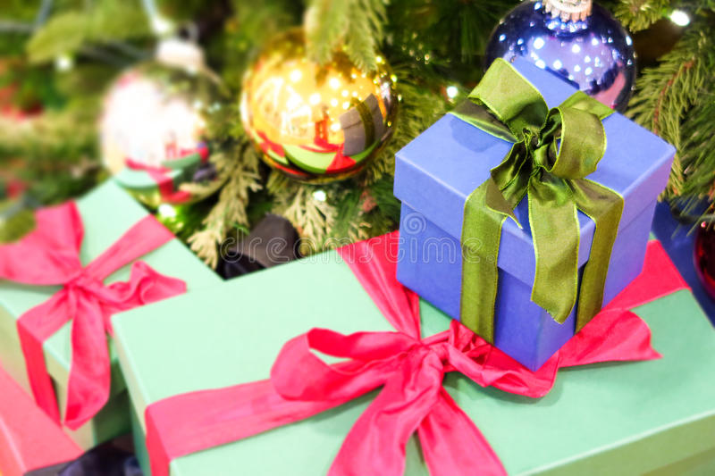 Christmas gifts. Xmas presents under a christmas tree - focus is on the bow of the blue box, copy space is to the left stock images