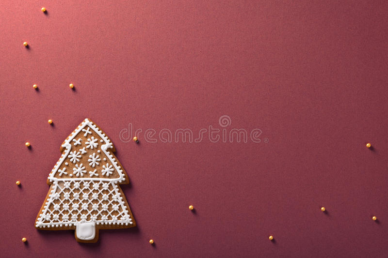Christmas gingerbread. Christmas tree gingerbread with golden balls on violet paper background royalty free stock images