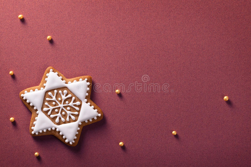 Christmas gingerbread. Christmas star gingerbread with golden balls on violet paper background royalty free stock images