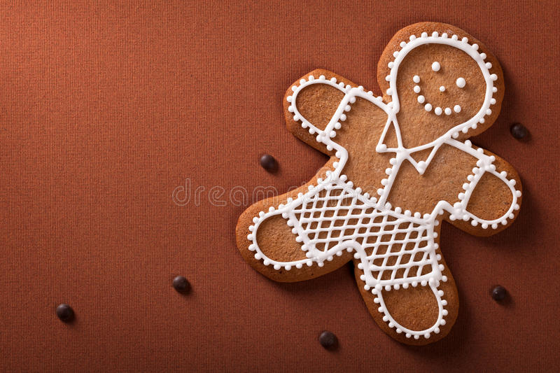Christmas gingerbread. Man with chocolate pills on brown paper background stock photo