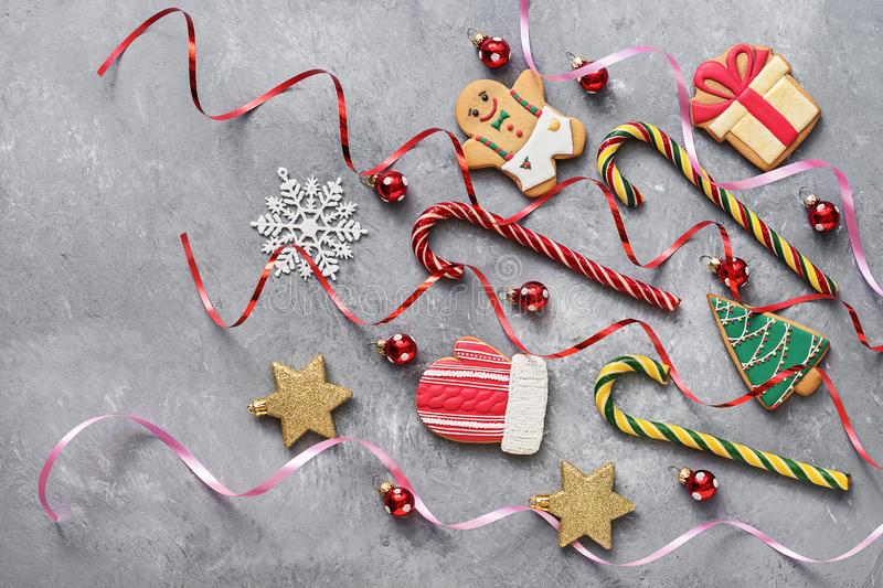 Christmas gingerbread cookies, candy cane, red balls, golden stars and snowflake on a gray textured background. Top view, flat lay.  royalty free stock photo