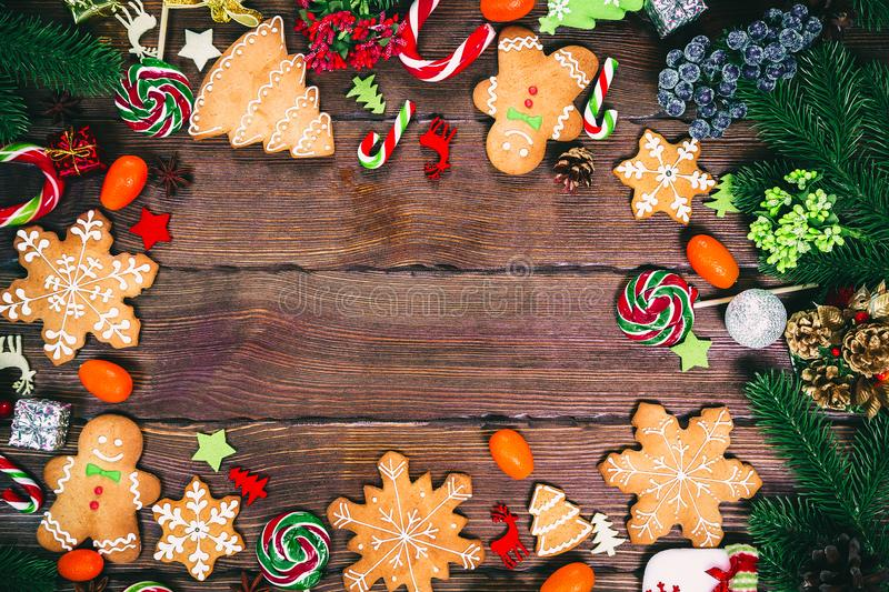 Christmas gingerbread cookies homemade on wooden table with candies, Christmas tree branches and New Year decorations. stock image