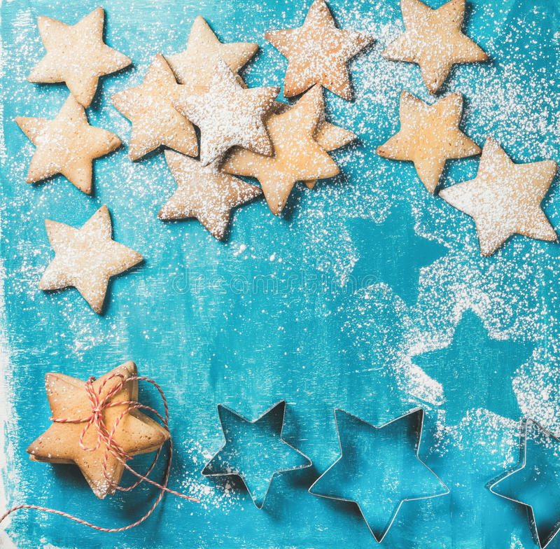 Christmas gingerbread cookies sprinkled with sugar powder on blue background royalty free stock image