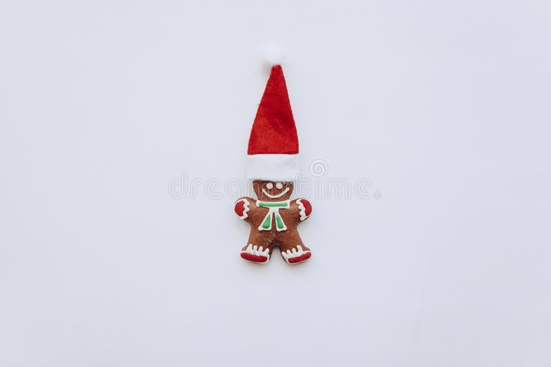 Christmas gingerbread in the form of a small ginger man in a red hat. Christmas or New Year`s concept in a minimal style royalty free stock image