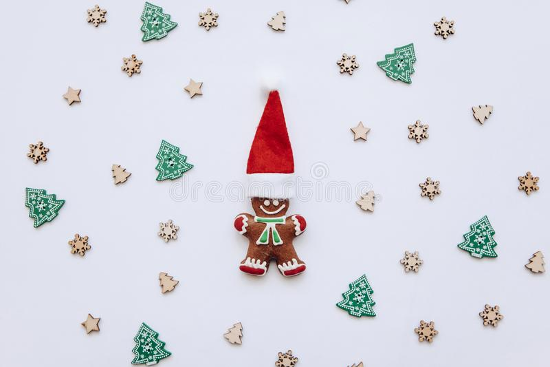 Christmas gingerbread in the form of a small ginger man in a red traditional hat on a decorated festive background. Christmas or New Year`s concept in a stock image