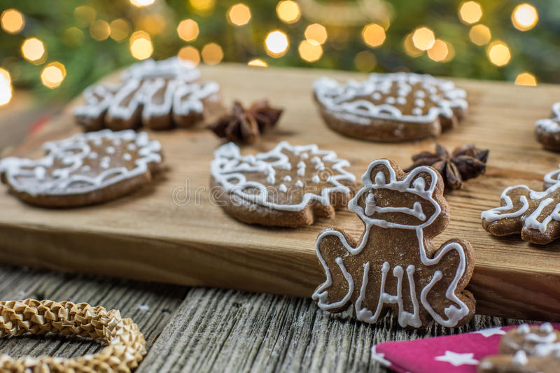 Christmas gingerbread frog with several other gingerbread. On wooden board royalty free stock photo