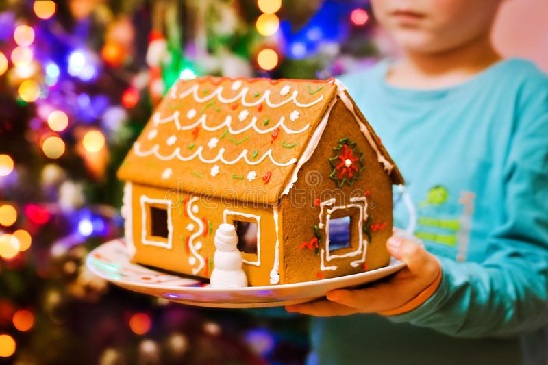 Christmas gingerbread house in children`s hands close-up against the backdrop of lights in the festive living room. stock photos