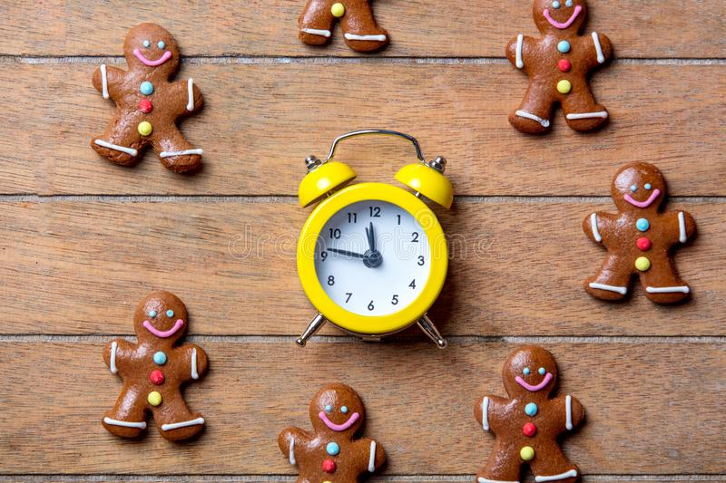 Christmas gingerbread man and alarm clock. On wooden table. Above view in old color style stock images
