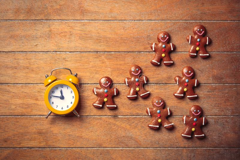 Christmas gingerbread man and alarm clock. On wooden table. Above view in old color style royalty free stock photo