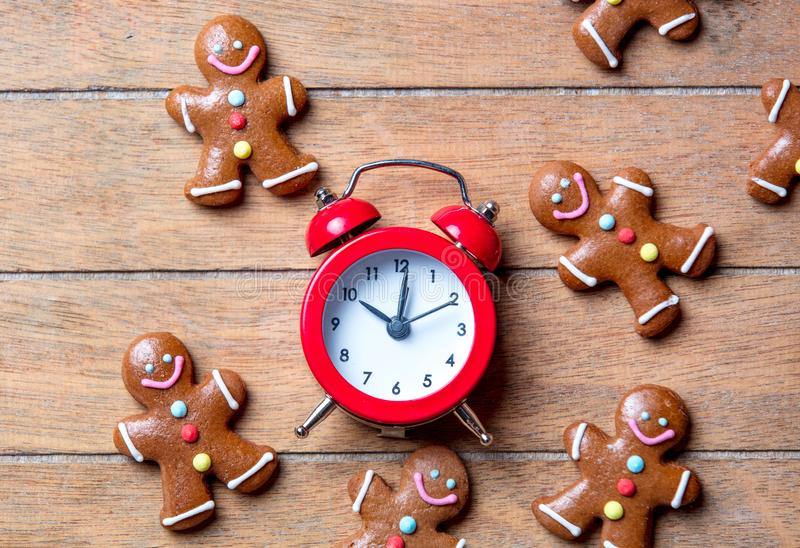 Christmas gingerbread man and alarm clock. On wooden table. Above view in old color style royalty free stock photography