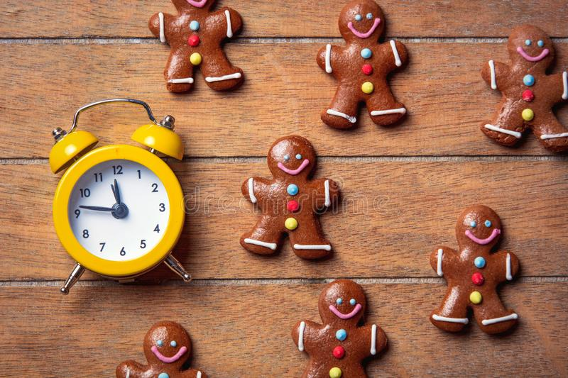 Christmas gingerbread man and alarm clock. On wooden table. Above view in old color style stock photos