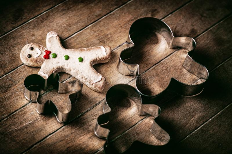 Gingerbread man cookie with baked forms. Christmas gingerbread man cookie with baked forms on wooden background stock photo