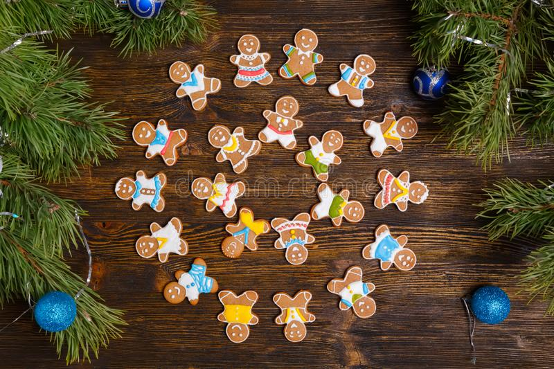 Christmas gingerbread man cookies decorated with icing. On wooden table, flat lay. Christmas and New Year traditions, winter holidays, homemade sweets, festive stock photography